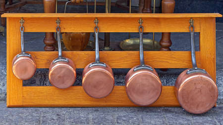 Copper pots cookware set at wooden rack