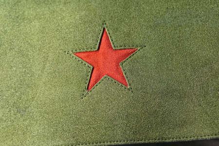 Red star symbol at green textile