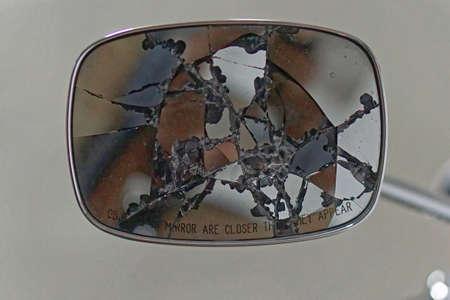 Broken glass rear view mirror at car