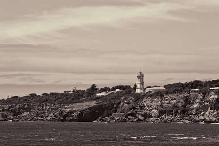 Light tower at shore near charm Boca do Inferno located close to the Portuguese city of Cascais. Stock Photo