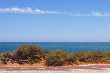 shore line: Cycleway on the Atlantic seaboard. Landscape with smooth ocean and blue sky. Stock Photo