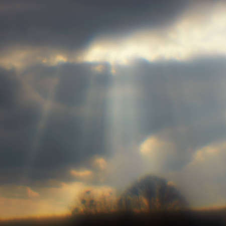Sun rays struck through the clouds. Photo made using monocle. Square format. Stock Photo