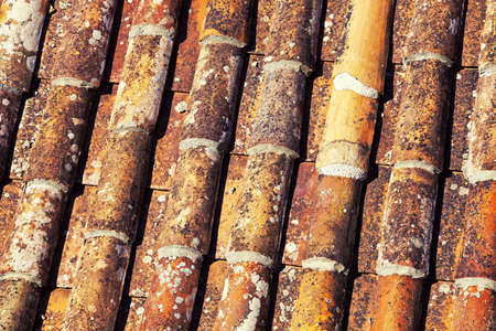 Close up of old, cylindrical red clay roof tiles on property.