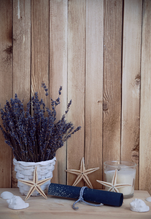 lavender in pots placed on a wooden shelf. decorated with starfish , seashells and candles