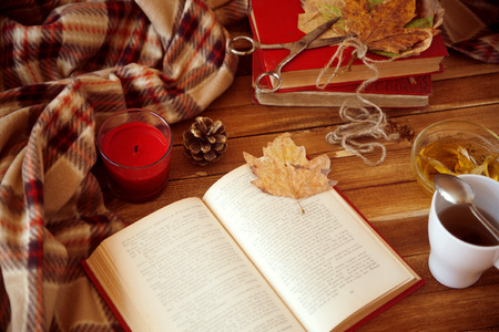 book lies on a wooden table, breakfast with green tea and honey, a cozy autumn morning