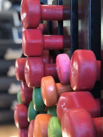 Many colorful dumbbells, lying in rows. 写真素材