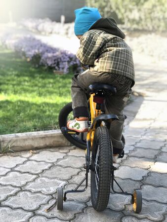The child sits on a bike in the park. Autumn sunny day. Stockfoto - 132120797