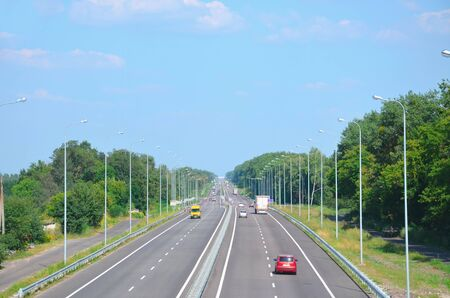 Kiev-Chop Highway in the afternoon with cars, two lanes in each direction, view into the distance.