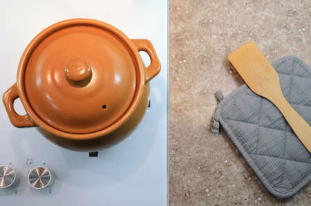 A ceramic pot stands on a white stove, potholder and a spatula lie on the table top, top view. Flat lay. Image