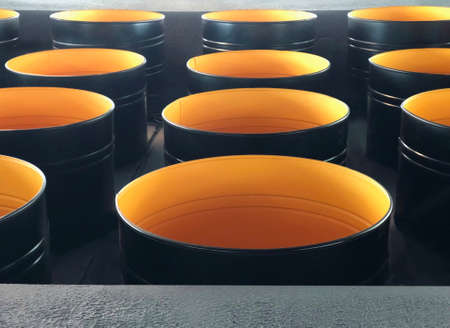 Many dark gray empty, open metal barrels, inside the yellow color, stand in rows. Image