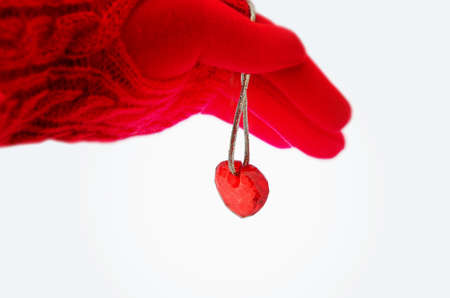 Female hand in a red glove holds a golden rope on which hangs a red glass heart. Isolated on white background. Image