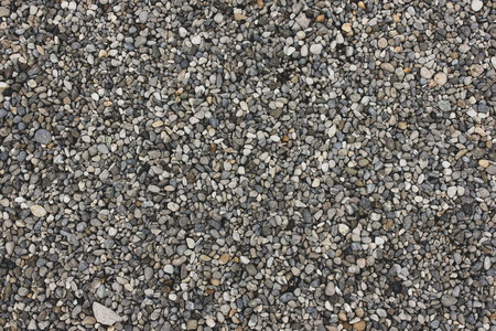Gray and white natural sand and stones texture of ground. Dotted grey rock floor with place for text