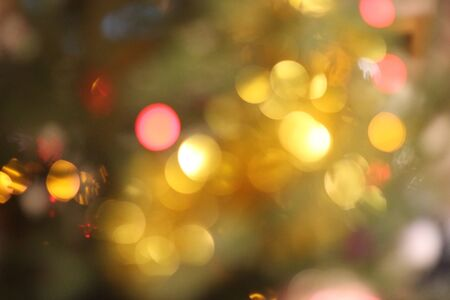 Beautiful grain and blurred holiday background with warm red and yellow glittering Christmas lights. Happy New Year image for winter decoration, banner design, with place for text