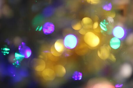 Grain and blurred holiday background with deep blue, purple and yellow glittering Christmas lights. Happy New Year image for winter decoration, banner design, with place for text 写真素材