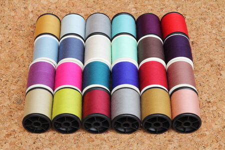 Spools of thread  multicolored on cork board photo