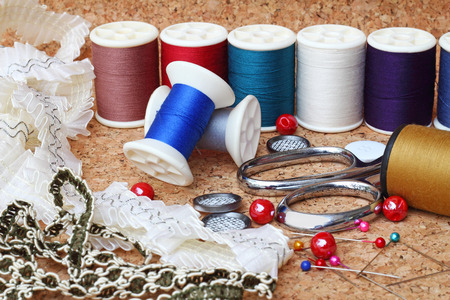 stitchwork: Sewing items  buttons, material, measuring tape, bobbins, buttons, cloth, safety pins, needles, spools of thread, scissors, lace Stock Photo