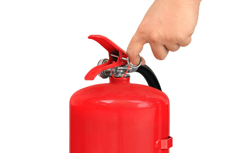 fire extinguisher: Hand pulling pin of fire extinguisher