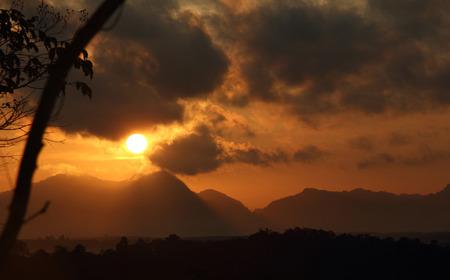 bright sun in an orange sky with dark clouds at sunrise Stock Photo