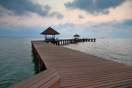 wooden bridge in the port between sunrise sky after hard rain Stock Photo