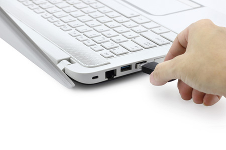 Hand connecting USB Flash drive to laptop computer on white background