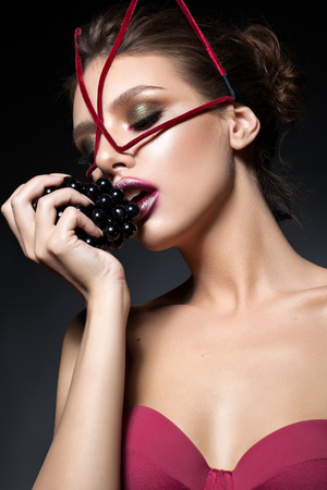 Beautiful young sexy model with fashion makeup, unusual face accessory and dark grapes in her hand on black background. Unusual red lips. Bright make up. Cat woman look