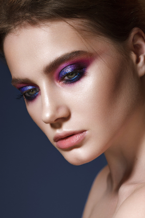 Beautiful young model with fashion make up, perfect skin. Trendy colorful smoky eyes. Lilac smoky eyes