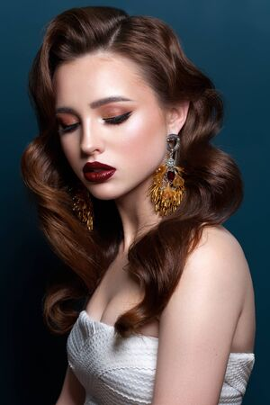Young beautiful girl with the fashion make-up, red lips, long designer earrings, wave hairstyle