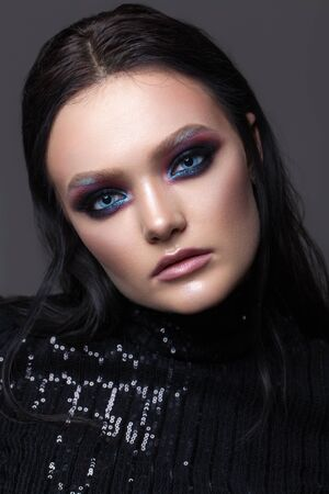 Attractive sexy girl with professional evening makeup, perfect shining skin, dark hair. Colorful smoky eyes. Фото со стока