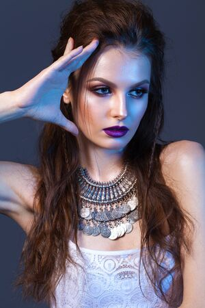 Attractive young model with professional make up, silver necklace, volume hairdo.