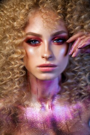 Beautiful blond model with a very volume curl hairstyle, colorful red smoky eyes and elements of body art
