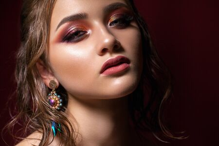 Attractive young model with colorful trendy smoky eyes, bright blue eyes, wet hairdo and fashion earring