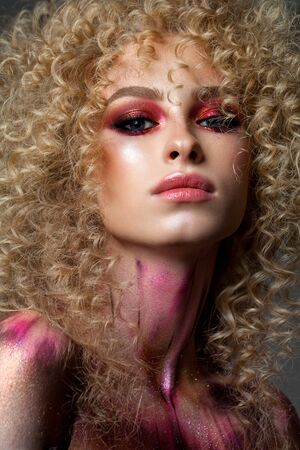 Attractive blond model with a very volume curl hairstyle, colorful red smoky eyes and elements of body art Banco de Imagens - 132120830