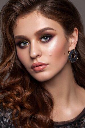 Belle jeune femme élégante avec maquillage de soirée et coiffure ondulée. Fards à paupières colorés