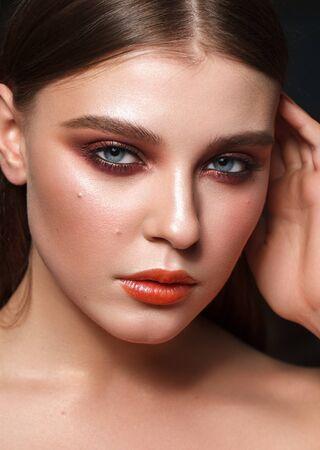 Modello perfetto con il trucco colorato professionale, pelle perfetta e occhi fumosi rossi. Ritratto del primo piano.