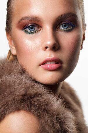 Ritratto di una giovane bellissima modella in abiti di pelliccia con pelle ideale, trucco professionale, ombretti blu e verdi.