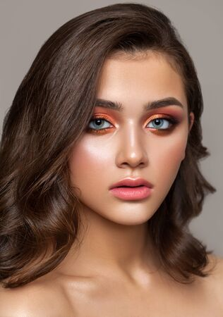 A very beautiful young girl with colorful trendy smoky eyes, bright blue eyes and natural wavy hairdo. Archivio Fotografico