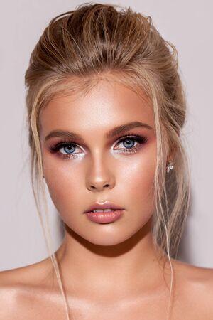 Jong blond meisje met zachte bruidsmake-up, perfecte huid, rijke wimpers en lokken die op het gezicht vallen.