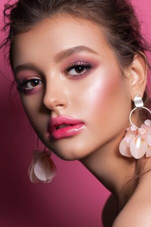 Modeporträt eines schönen Mädchens mit trendigem rosa Make-up, Accessoires und Hintergrund. Brünettes Model mit haselnussbraunen Augen