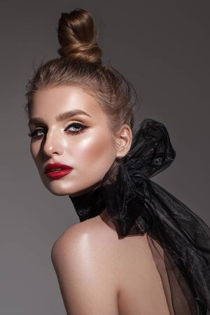 Fashion portrait of beautiful young model with professional makeup, perfect skin and black organza scarf.