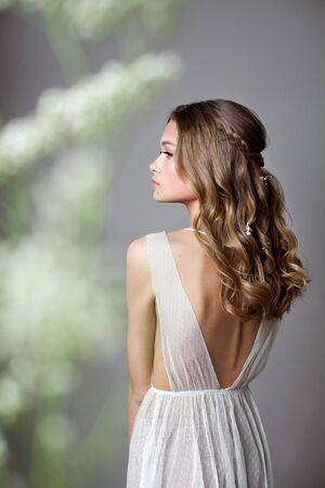 Foto von der Rückseite eines sehr schönen jungen Models im Brautkleid mit Schleierkrautblüten in den Händen. Romantischer Stil