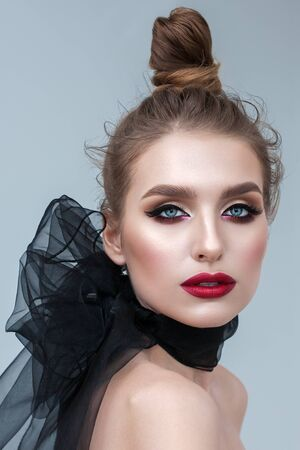 Fashion portrait of beautiful young model with professional makeup, perfect skin and black organza scarf on her neck.