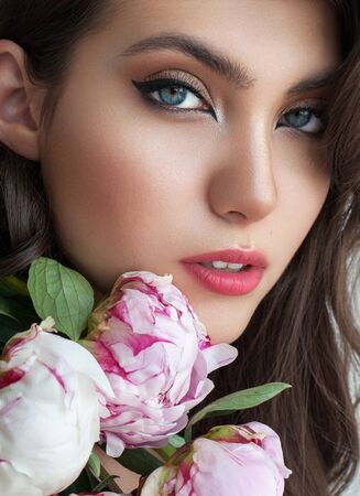 Close up portrait of a very beautiful brunette model with professional day makeup, perfect skin and Natural flowers. Stock fotó