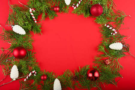 Christmas frame made of green branches, festive decorations and pine cones on red table. Stock fotó
