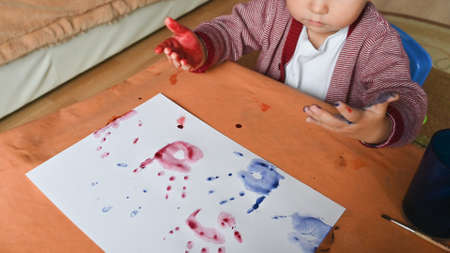Top view of colored handprints on a sheet of paper. Boy draws color paints. Developing activities at home. Stock Photo