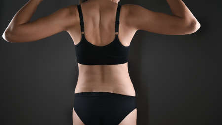 Caucasiana woman showing her biceps muscles on the arms in black sport underwear over gray background. Gropped view with copy space
