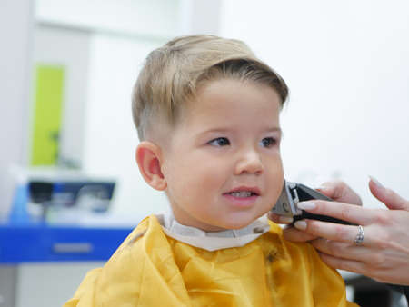 Little pretty boy had his first trendy haircut at barbershop. Portrait of serious 2 years child
