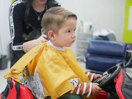 Caucasian 2 years old boy had his first trendy haircut at barbershop. Zdjęcie Seryjne