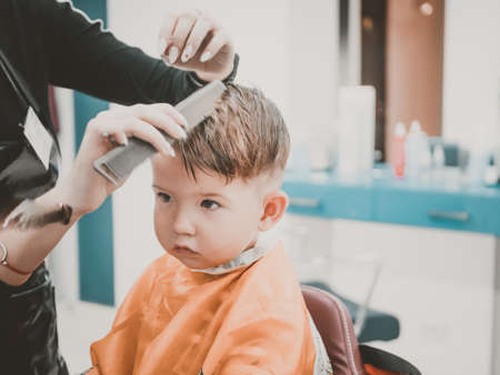 Caucasian 2 years old boy had his first trendy haircut at barbershop.