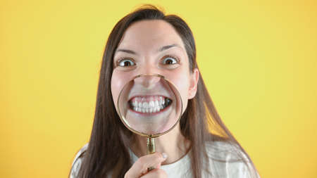 Funny caucasian woman showing her teeth with magnifying glass, standing over yellow background. Crooked teeth correction concept