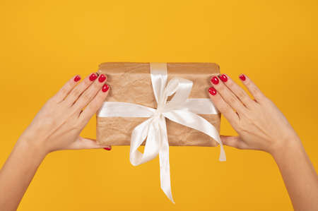 Cropped female hands with perfect red manicure holding wrapped gift box over yellow background. Gift delivery concept. High quality photo